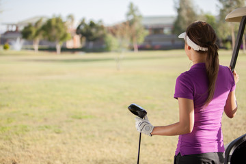 Young female golfer looking at the golf course with copy space