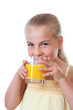 little girl drinking a glass of orange juice