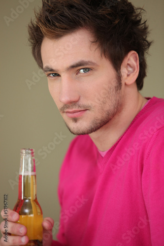 Young man with a bottle of lager
