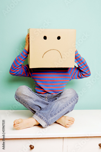 Leinwanddruck Bild Trauriges Kind in einem Karton