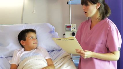 Female Doctor Talking To Boy In Hospital Bed