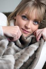 Blond woman relaxing under blanket