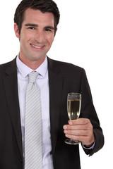 Confident businessman holdingvchampagne