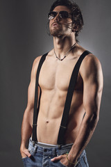 Studio shot of a sexy man with suspenders and sunglasses