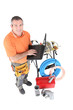 Workman posing with his laptop, tools and building materials