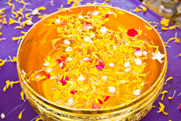 Water in bowl mixed with perfume and  flowers