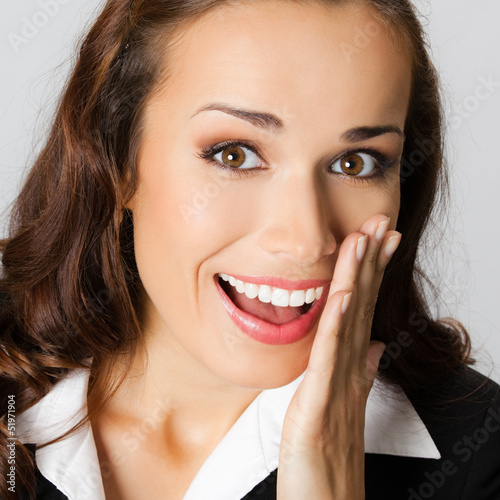 Businesswoman covering mouth, over gray