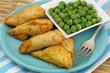 Vegetarian samosas and green peas, close up