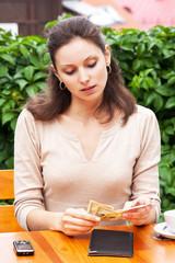Девушка в кафе оплачивает счет наличными