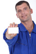 Man in blue overalls holding a business card left blank