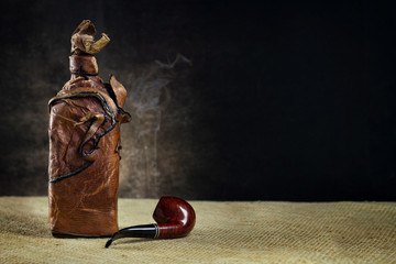 Leather vintage bottle with a pipe on a dark background