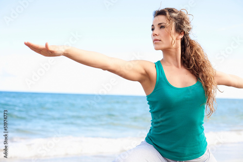 young beautiful female doing yoga on the beach