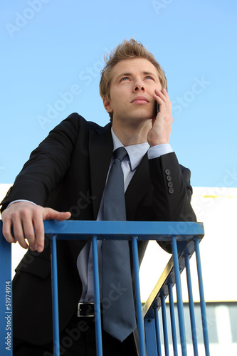 Young businessman using his phone outside