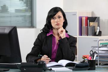 Brunette office worker thinking