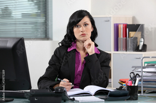 Brunette office worker thinking