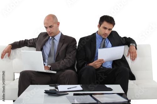 Two executives sitting on white sofa