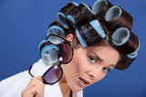 Woman with her hair in rollers holding a pair of sunglasses - 51976138
