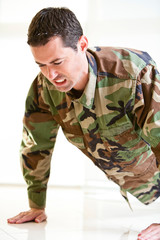 White male in army uniform straining doing a push up