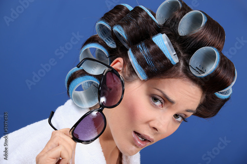 Woman with her hair in rollers holding a pair of sunglasses
