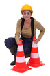 Woman kneeling by traffic cones