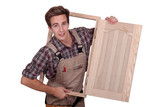 Carpenter holding cupboard door