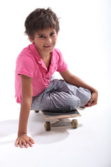 Little boy sat on skateboard