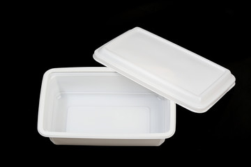 open white plastic food container over black background