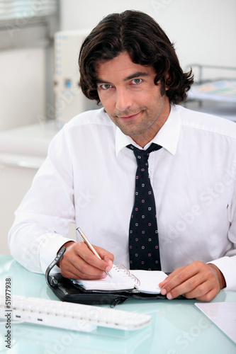 Businessman writing in a diary