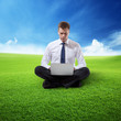 business man with notebook sitting on grass