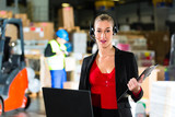Woman using headset and laptop at warehouse
