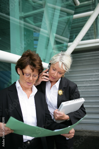 two senior businesswoman hammering-out a deal