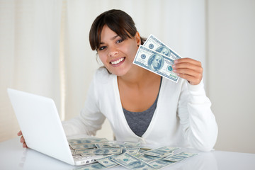 Smiling young woman showing you cash money