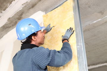 Man fitting wall insulation
