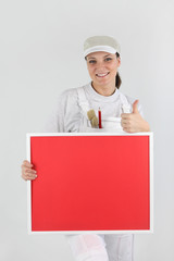 Female decorator with a board left blank for your message