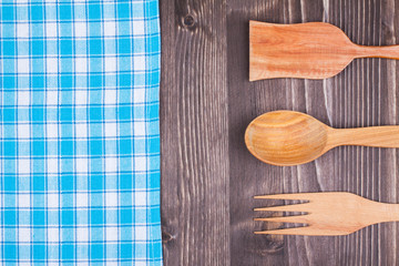 Blue and white checkered tablecloth, fork, spoon on wood