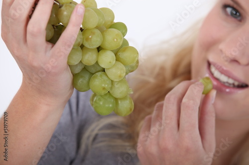 Attractive blond woman eating bunch of grapes