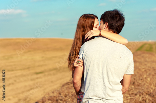 Young attractive couple in love kissing in summer in field