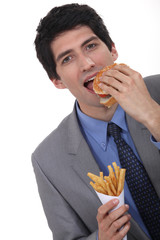 Businessman eating burger and fries