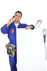 Electrician with a telephone and a board for message