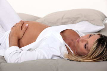 A pregnant woman lying in bed.