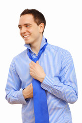 Businessman at home making his tie
