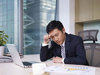 asian businessman thinking in office, frustrated