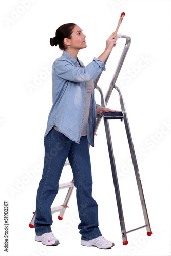 Female decorator stood by step-ladder