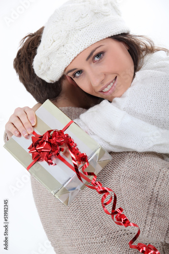 Couple hugging with gift in hand