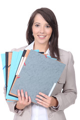 Female office worker with a pile of paperwork
