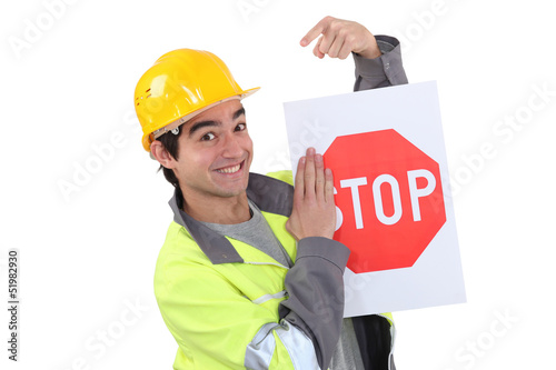 Traffic worker pointing to stop sign