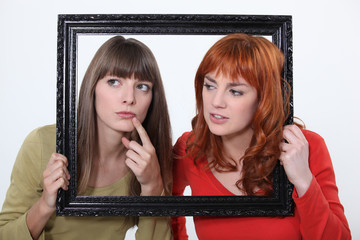 girls behind a wooden frame