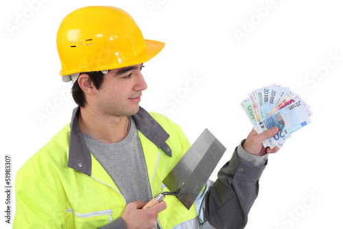 Young builder with a handful of cash