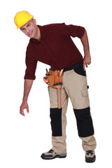 Tradesman bending over to pick something up