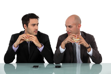 Two businessmen sat eating hanburgers